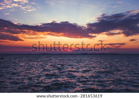 Dramatic sunset on a calm the sea with reflection - stock photo