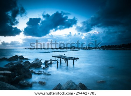 Dramatic sunset on the Mediterranean Sea, the pier was destroyed by storms. Tinted - stock photo