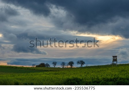 Dramatic sunset over a green field - stock photo