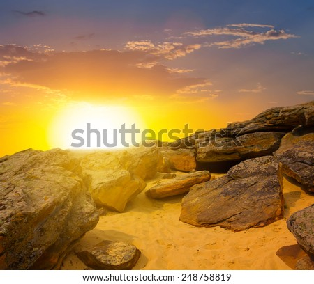 dramatic sunset over a stony desert - stock photo