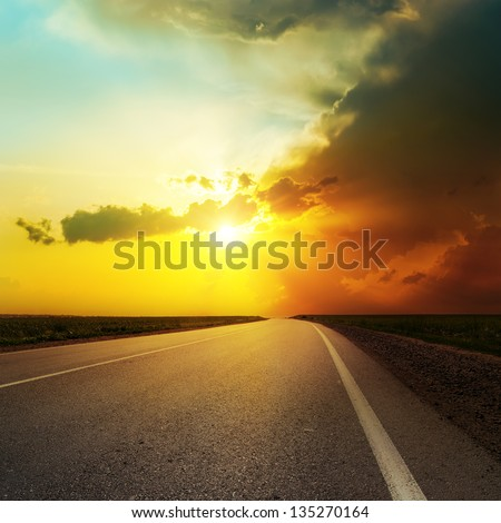 dramatic sunset over asphalt road