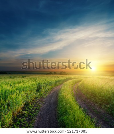 dramatic sunset over dirty road to horizon - stock photo