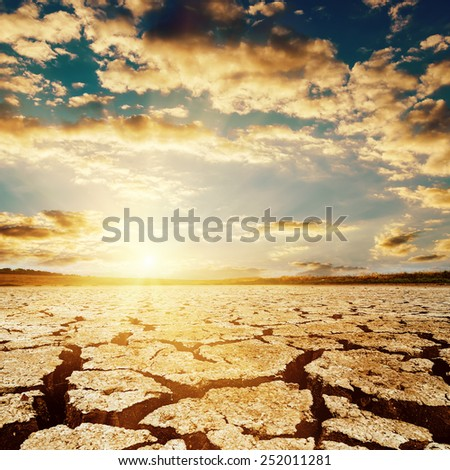 dramatic sunset over drought earth - stock photo