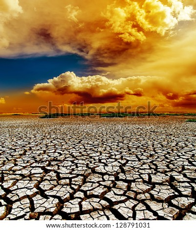 dramatic sunset over dry cracked earth - stock photo