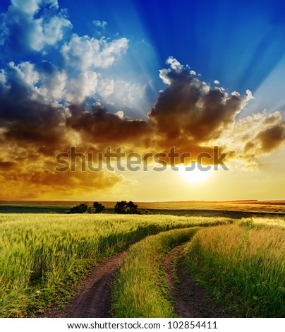 dramatic sunset over rural road - stock photo