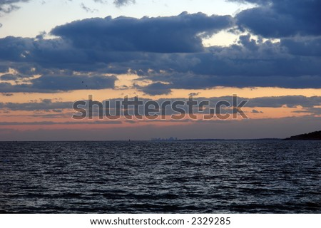 dramatic sunset over the atlantic ocean with deep thick clouds and ripples of the sea drawing the eye to the land mass in the background and the boston skyline - stock photo