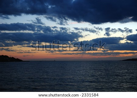 dramatic sunset over the atlantic ocean with deep thick clouds and ripples of the sea drawing the eye to the land mass on either side with the boston skyline in the distance - stock photo