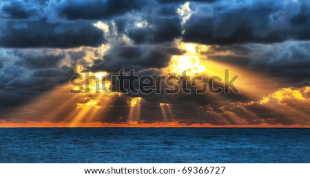 Dramatic sunset rays through a cloudy dark sky over the ocean. - stock photo