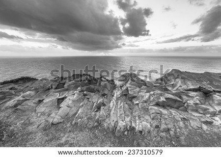 Dramatic sunset rays through a cloudy dark sky over the ocean. Black and white  - stock photo