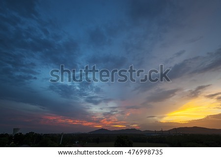 Dramatic sunset sky with orange and blue colored clouds.