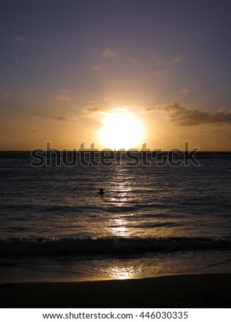 Dramatic Sunset through the clouds and reflecting on the Pacific ocean on the water lapping on the beach in Waikiki of Oahu, Hawaii. - stock photo