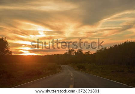 Dramatic sunset view from the asphalt road in the countryside. (soft focus) - stock photo