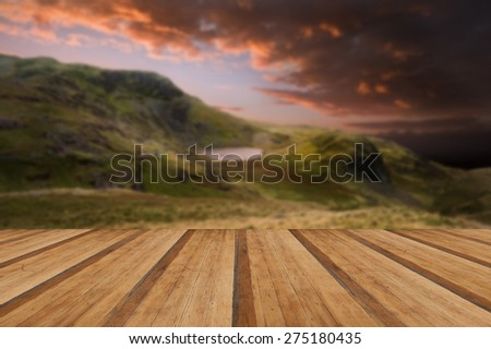 Dramatic sunset with beautiful sky over mountain range giving a strong moody landscape with wooden planks floor - stock photo