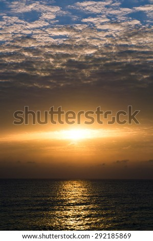Dramatic sunset with dark clouds in the sea - stock photo