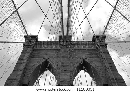 Dramatic, symmetrical, black and white photo of the tower and cables of the Brooklyn Bridge in New York City.