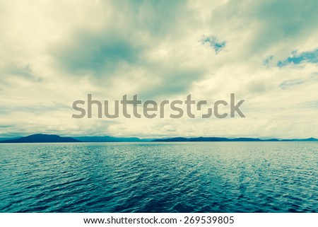 Dramatic tropical sea in cloudy day. Retro filter. - stock photo