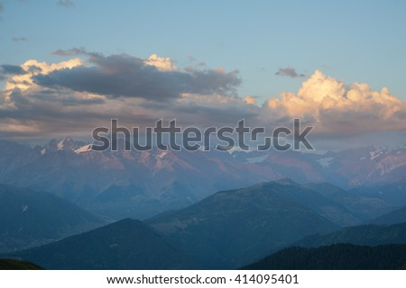 Dramatic view at the Caucasian ridge. Beautiful sunset in the mountains. Mountains silhouettes and clouds highlighted by the sun. Svaneti, Georgia. - stock photo