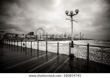 Dramatic view from Brighton pier during rainy day - black and white photo - stock photo
