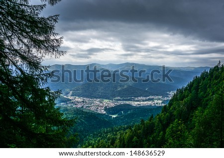 Dramatic view of Busteni town from the mountains, with grey sky and mist in forest. - stock photo