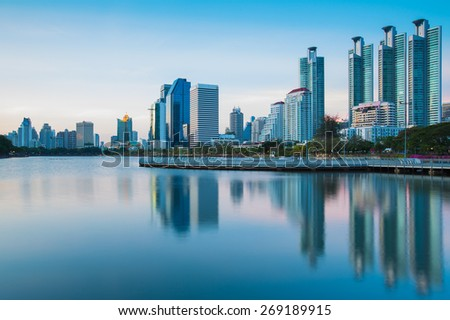 Dramatic view of commercial building in Bangkok twilight with water reflection - stock photo