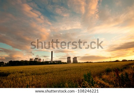 Dramatic view of Fiddler's Ferry coal burning power station, England. Cooling towers in the evening light with a cloudscape and field of wheat in the foreground - stock photo