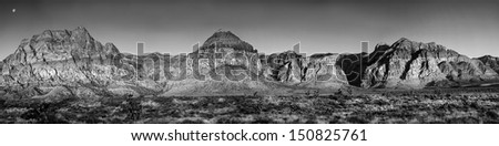 Dramatic view of Red Rock Canyon in Nevada at sunrise showing the moon still in the sky - stock photo