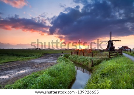 dramatic warm sunrise over Dutch windmill  and river, Groningen, Netherlands