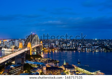 Dramatic widescreen panoramic image of the city of Sydney at night including the Rocks, Bridge and Luna Park and a broad view of the water in the harbour - stock photo