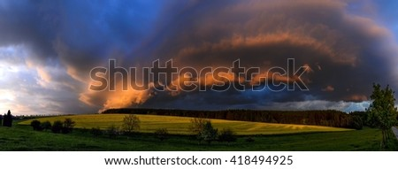 dramatically evolving the cloudy formation lit by the setting sun over the meadow and a field with blooming rape,Zabrehs highlands, North Moravia, Czech republic, panoramic view compiled from six shot