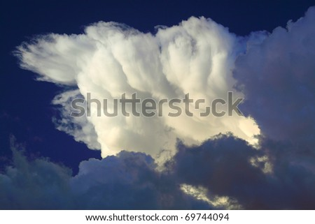 Dramatically illuminated clouds in the evening sky - stock photo