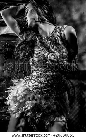 Dramatized image of sensual & attractive young woman in luxury dress posing outdoors. Black-white photo.