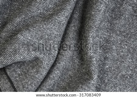Draped herringbone tweed background with closeup on wool fabric texture - stock photo