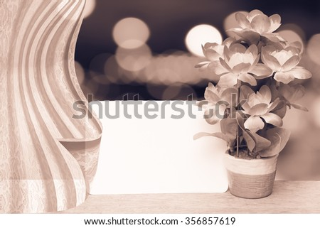 drapery on white card and flower vase with bokeh light in shopping mall