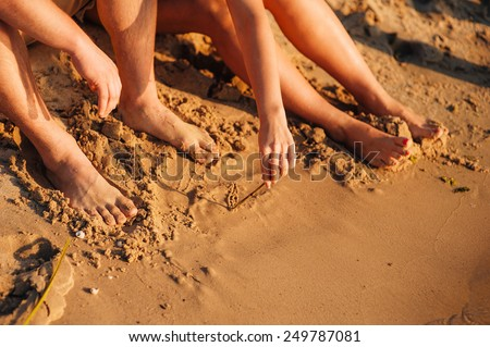 Draw a heart on the sand. Couple in love on the beach. Feet close-up. Expresses love. Heart drawn in the sand - stock photo