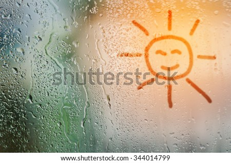 draw sun on natural water drops glass window background - stock photo