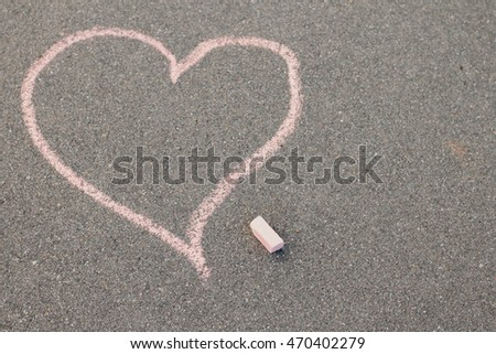 drawing a heart and love letters in chalk on the pavement