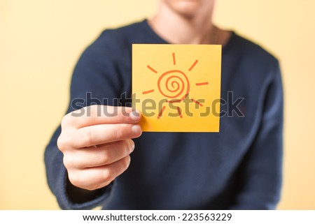 drawing a picture in his hand sun - stock photo