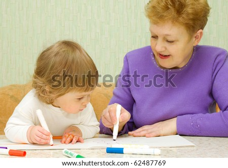 Drawing baby with her grandma at home - stock photo