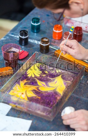 Drawing beautiful marbling pattern with inks and stick - stock photo