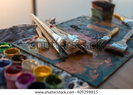 Drawing classes tools in art studio. Angle view photo of paintbrushes lying on palettewith oil paints brushstrokes mixture. - stock photo