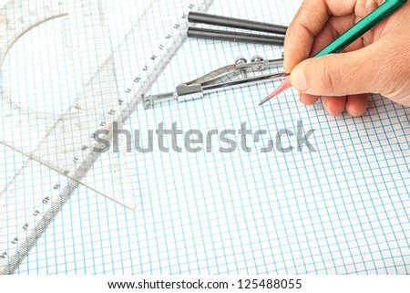drawing compass , pencil, and ruler in the grid sheet studio shoot - stock photo