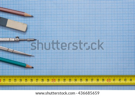 drawing compass, pencil, and ruler on graph paper background - stock photo