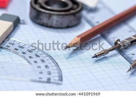 drawing compass, pencil, and ruler on graph paper background