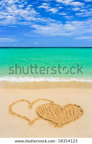 Drawing connected hearts on beach - love concept - stock photo