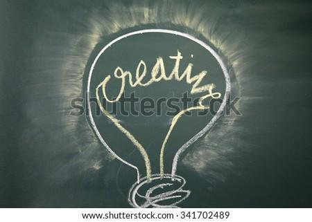 drawing-creative light bulb on blackboard - stock photo