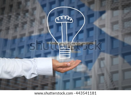 Drawing graphics lamp or bulb on hand to concept Creativity of new ideas in business and have skyscraper background.