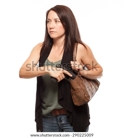 Drawing gun from holster in her concealed carry purse   Attractive female shooter holding weapon against white background. - stock photo