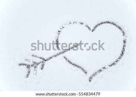 drawing heart and arrow on white snow background