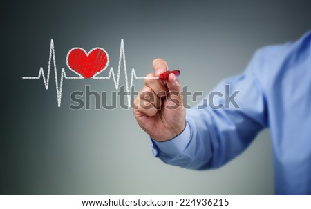 Drawing heartbeat graph on screen with a pen concept for healthy lifestyle pulse trace - stock photo