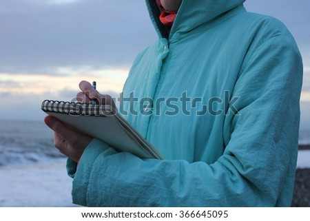Drawing in a notebook on the waterfront.  - stock photo